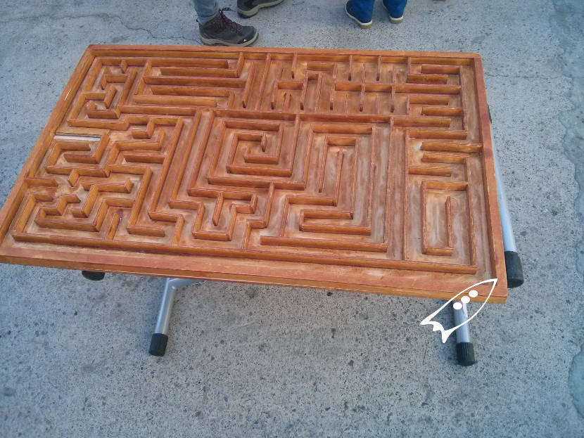 Large wooden maze that has to be moved between 2 people