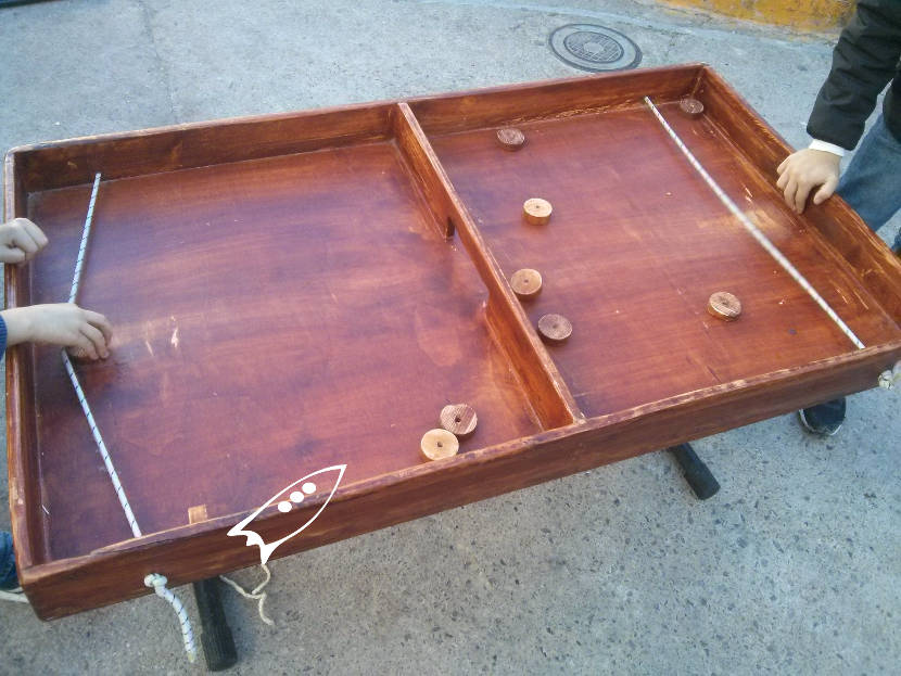 Similar to the recreational air hockey game but without air and using rubber bands